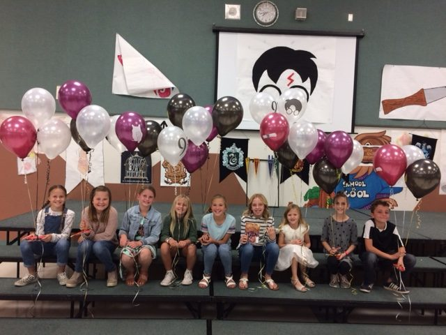 Storytelling Festival Winners Pose On Bleachers With Balloons